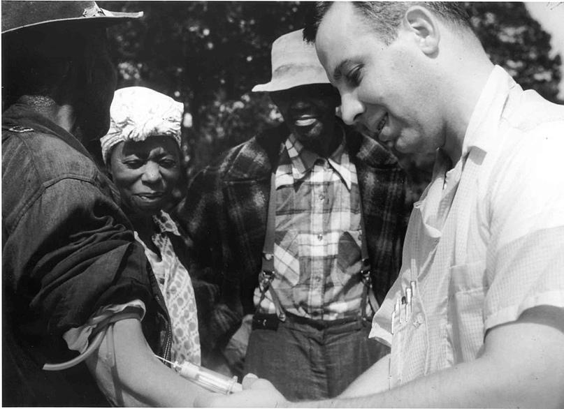 Доктор берет кровь на анализ у одного из участников эксперимента по заражению людей сифилисом